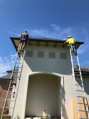 front view of home with men on ladders installing seamless gutters